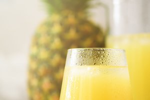 Pineapple juice in glassware and whole pineapple fruit on gray background. Copy space, sunlight effect. Summer, holiday concept. Raw, vegan, vegetarian, clean eating diet.