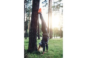 Young sporty woman doing handstand leaning straight legs on tree practicing in the woods
