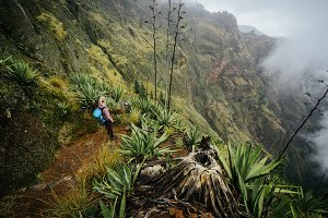Female traveler staying on the cove volcano edge above the foggy green valley overgrown with agaves Santo Antao island in Cabo Verde