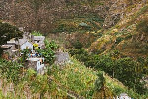 Local stone houses of small village between lush green vegetation and mountain landscape. Santo Antao Cape Verde