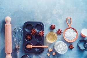 Making pastry concept with baking tools and ingredients on a modern concrete background with copy space. Scoops, whisks, cookie cutters, muffin tin, sugar, flour, anise stars and cinnamon from above.