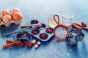 Baking utensils header. Muffin tin, sea salt, eggs, flour, oil and sugar with whisks and cookie cutters on a modern concrete background with copy space. Making pastry concept.