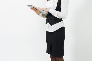Full length of beautiful caucasian young brown-hair business woman in black suit, white shirt and glasses with tablet isolated on white background. Manager or worker. Copy space for advertisement.