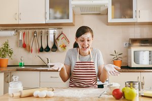 A young funny cheerful woman sitting at a table with flour and going to prepare a Christmas cakes in the kitchen. Cooking home. Prepare food.