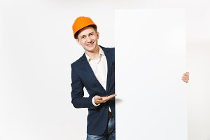 Young smiling businessman in dark suit, protective hardhat holding big white empty blank material with place for text or image and pointing hand aside on copy space isolated on white background.