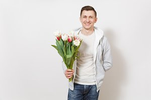 Young handsome happy smiling man student in t-shirt and light sweatshirt holds bright bouquet of white and pink tulips in his hands isolated on white background. Concept of celebration, good mood
