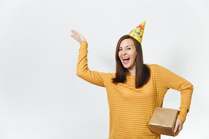 Fun young happy woman in yellow clothes, birthday party hat holding golden gift box with present, celebrating holiday, pointing hand away on white background isolated, copy space for advertisement.