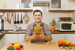 Handsome fun caucasian young man in apron, brown shirt sitting at table, throwing up vegetable salad in bowl in light modern kitchen. Dieting concept. Healthy lifestyle. Cooking at home. Prepare food.