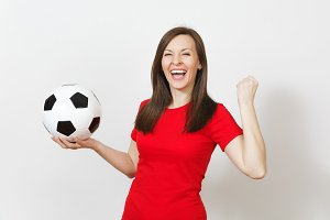 Overjoyed European young woman, football fan or player in red uniform holding soccer ball, doing winner gesture isolated on white background. Sport, play football, cheer, healthy lifestyle concept.