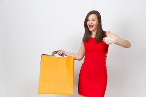 Attractive glamour fashionable young woman in red dress holding multi colored packets with purchases after shopping isolated on white background. Copy space for advertisement. With place for text.