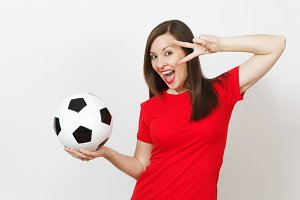 Pretty European young woman, football fan or player in red uniform holding classic soccer ball, fingers near eye isolated on white background. Sport, play football, health, healthy lifestyle concept.