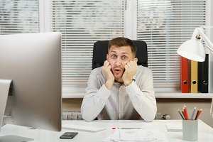 Shocked perplexed and stress business man in shirt sitting at the desk, working at computer with modern monitor, folders, lamp, documents in light office on window background. Manager or worker.