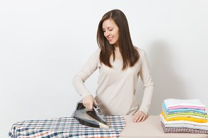 Young attractive housewife in light clothes ironing shirt of her husband, clothing on ironing board with iron. Woman isolated on white background. Housekeeping concept. Copy space for advertisement.