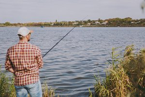 Back view Young unshaven man with fishing rod in checkered shirt, cap and sunglasses casts bait and fishing on lake from shore near shrubs and reeds. Lifestyle, recreation, fisherman leisure concept.
