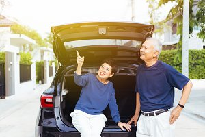 Happy Asian senior couple standing on the back of SUV car, pointing up in the sky with smile and happiness
