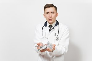Sad upset shocked handsome young doctor man isolated on white background. Male doctor in medical uniform, stethoscope holding packing tablets, pills. Healthcare personnel, health, medicine concept.