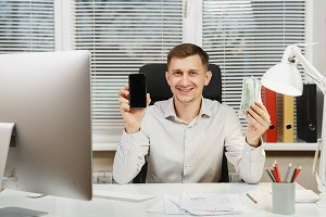 Smiling business man in shirt sitting at the desk with mobile phone and lot of cash money, working at computer with modern monitor, documents in light office on window background. Manager or worker.