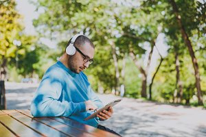 Young happy man, businessman or student in casual blue shirt glasses sitting at table with headphones, tablet pc in city park, listen music, rest outdoors on green nature. Lifestyle leisure concept.
