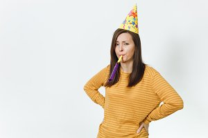 Pretty caucasian sad young woman in yellow clothes and birthday party hat with brown long hair, playing pipe, celebrating holiday alone without present on white background isolated for advertisement.