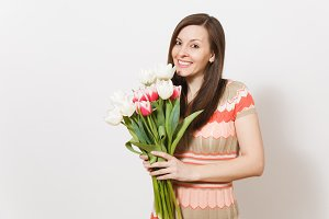 Beautiful young happy brunette woman in light patterned dress is holding bouquet of white and pink tulips in hands, smiling and rejoices in studio on white background. Concept of holiday, good mood.