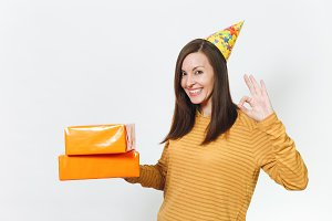 Beautiful fun young happy woman in yellow clothes, birthday party hat holding orange gift boxes with present, celebrating holiday, showing OK gesture on white background isolated for advertisement.