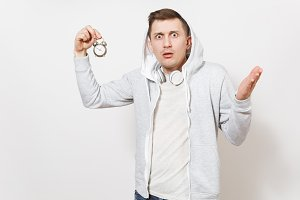 Young shocked embarrassed guy in t-shirt and light sweatshirt with hood with headphones holds small alarm clock and shows it isolated on white background. Concept of pastime. Time is running out