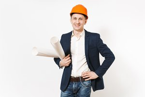 Young satisfied businessman in dark suit, protective orange hardhat holding blueprints plans and keeping arm at waist isolated on white background. Male worker for advertisement. Business concept.