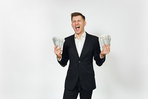 Young successful handsome rich business man in black suit holding wad of cash dollars isolated on white background for advertising. Concept of money, achievement, career and wealth in 25-30 years.