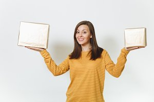 Beautiful caucasian fun young happy birthday woman in yellow clothes holding two golden gift boxes with present, celebrating and enjoying holiday party on white background isolated for advertisement.