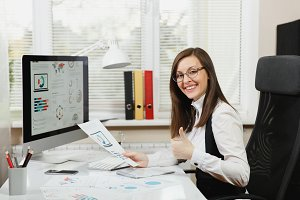 Beautiful smiling brown-hair business woman in suit and glasses sitting at the desk with cup of coffee, working at computer with documents in light office, looking at the camera and showing thumb up