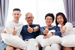 Asian family with adult children and senior parents giving thumbs up and relaxing on a sofa at home together. Happy family time together