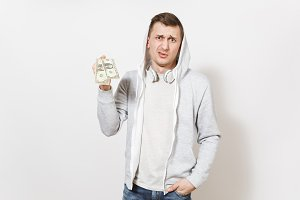 Young handsome man student in t-shirt, blue jeans and light sweatshirt with hood with headphones holds two one-dollar bills and perplexedly looks isolated on white background. Concept of emotions
