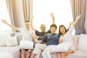Asian family with adult children and senior parents raising hands up and sitting on a sofa at home. Happy and relaxing family time