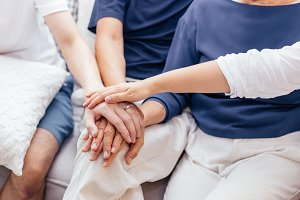 Close up of family with adult children and senior parents putting hands together and sitting on sofa at home together. Family unity and cooperation concept