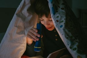 Boy reading with a flashlight