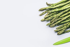 Green asparagus with kitchen knife
