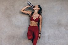 Female athlete drinking water by Jacob Lund in Sports