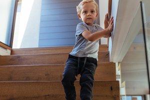 Little boy alone walking down stairs