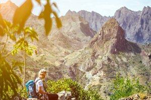 Girl resting on the hiking trail leading through arid rocky terrain towards Coculli village on Santo Antao Cape Verde
