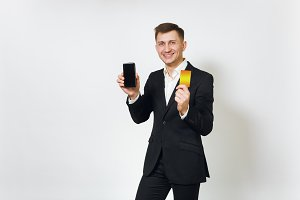 Young successful handsome business man in black suit holding golden credit card and mobile phone isolated on white background for advertising. Concept of money, achievement and wealth in 25-30 years.