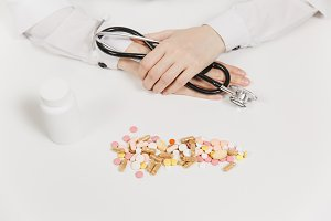 Doctor at white desk with handful pills in office in hospital. Woman holds in hands stethoscope in consulting room. Medicine concept. Copy space advertisement. With place for text. Advertising area.