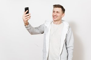 Young handsome smiling man student in t-shirt, blue jeans and light sweatshirt takes himself on phone during call with headphones in studio on white background. Concept of communication, good mood