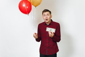 Handsome caucasian sad upset young y man in red plaid shirt with yellow golden balloons, one dollar banknote celebrating birthday, on white background isolated for advertisement. Holiday, pure concept