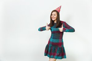 Pretty caucasian young woman in plaid dress and birthday party hat with charming smile, celebrating holiday showing thumbs up on both hands copy space isolated over white background for advertisement.