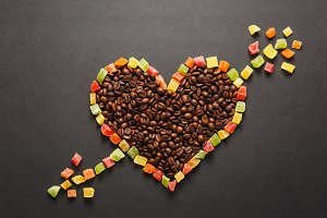 Candied fruits in the form of heart with arrow, brown coffee beans isolated on black background for design. Saint Valentine's Day card on fabruary 14, holiday concept. Copy space for advertisement.
