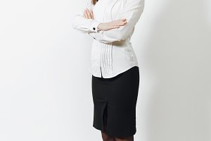 Full length of beautiful European young smiling brown-hair business woman in white shirt, black skirt holding hands crossed isolated on white background. Manager, worker. Copy space for advertisement.