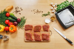 Raw meat. Pieces fresh beef, lamb or pork tenderloin on cutting board on wooden table with different vegetables, spices, mushrooms, baking tray, knife. Top view flat lay. Copy space for advertisement.