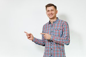 Handsome cheerful positive satisfied caucasian smiling fun young happy man 25-30 years in blue plaid shirt pointing index fingers aside on white background isolated, copy space for advertisement.