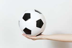 Female hands holding soccer classic white black ball isolated on white background. Sport, play football, health, healthy lifestyle concept.