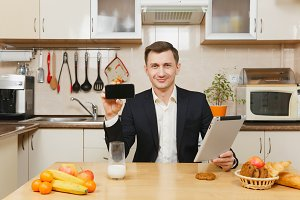 Handsome young business man in suit, shirt, having breakfast, sitting at table with tablet, showing mobile phone, eating fruits on light kitchen. Healthy lifestyle. Cooking at home. Prepare food.